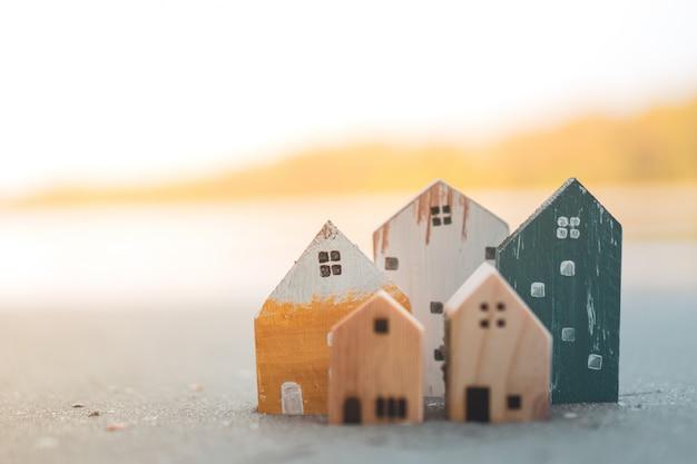 Gesloten kleine huismodellen op zand met zonlicht en strand.