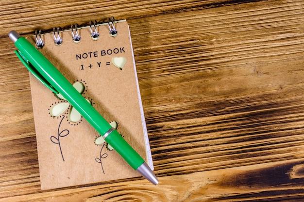 Gesloten kleine kladblok en balpen op rustieke houten tafel. bovenaanzicht