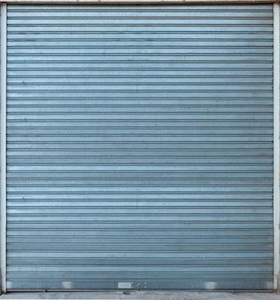 Gesloten metalen sluiter op een winkel, ideaal voor achtergronden en texturen