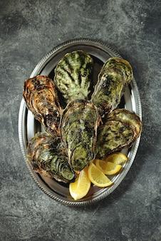 Gesloten oesters met plakjes citroen op een bord