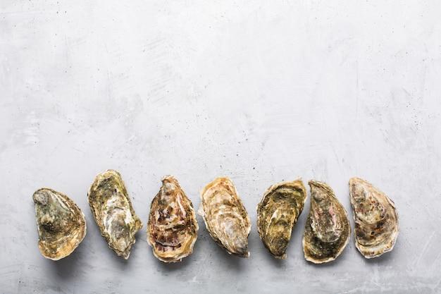Gesloten oesters op grijze betonnen achtergrond. gezonde zeevruchten. kopieer ruimte
