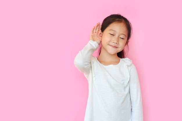 Gesloten ogen aziatisch klein kind meisje lachend met hand over oor luisteren en horen van geruchten of roddels over roze geïsoleerde achtergrond