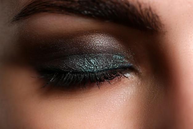 Gesloten ogen van mooie vrouw die partijmake-up draagt