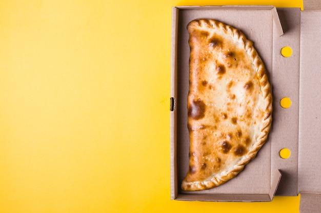 Gesloten pizza calzone in verpakkingsdoos op gele achtergrond.