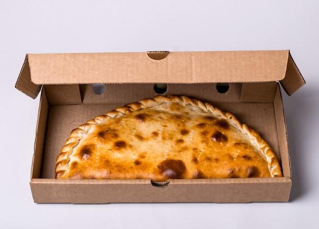 Gesloten pizza calzone in verpakkingsdoos op grijze achtergrond.