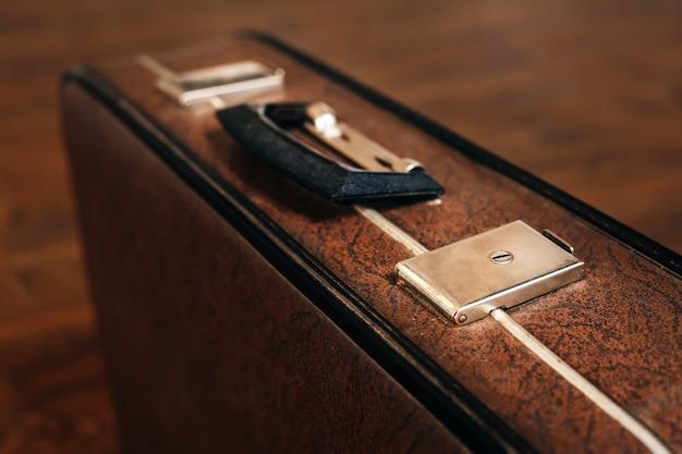 Gesloten retro koffer op de houten vloer.