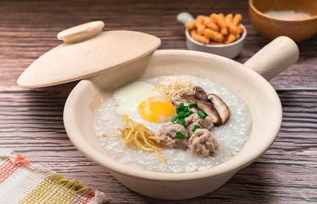 Gesloten rijst congee bedekt zacht gekookt ei gekookt varkensvlees pasteitje ballen gember en shiitake paddenstoel op witte klei pot bijgerecht door knapperige gefrituurde deegstok
