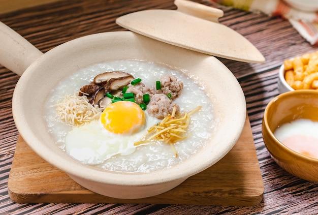 Gesloten rijstepap met zacht gekookt ei en gehaktbal bekend als thais ontbijt