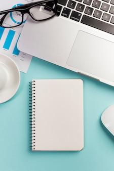 Gesloten spiraalvormige blocnote met laptop en oogglazen op blauw bureau