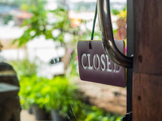 Gesloten teken boord opknoping op glazen deur
