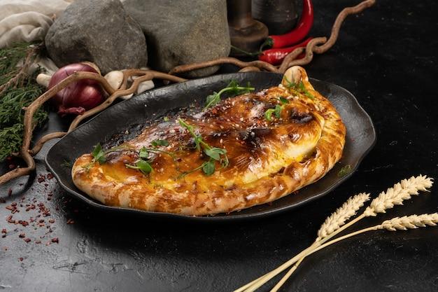Gesloten vegetarische pizza calzone op een zwarte plaat