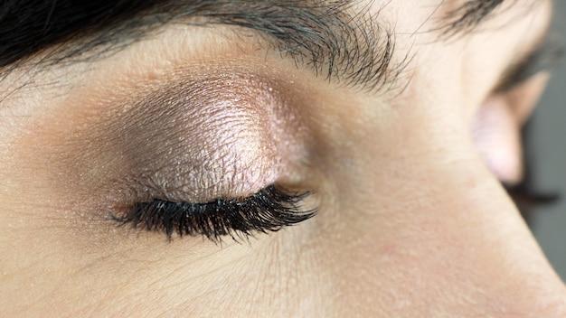 Gesloten vrouwelijk oog, hangende wimpers, grijze achtergrond. close-up.