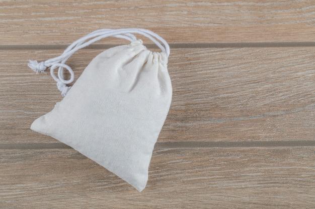 Gesloten witte zak vol maïskorrels op een houten tafel.