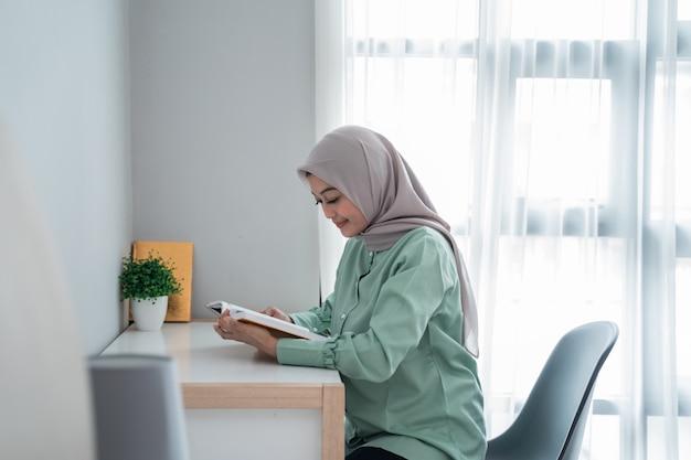 Gesluierde jonge vrouw houdt het heilige boek van de koran vast