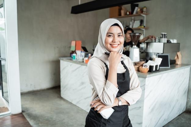 Gesluierde serveerster meisje met een glimlach pose