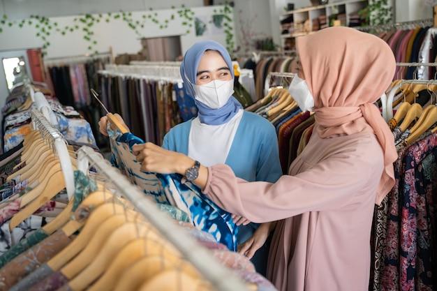 Gesluierde serveersters dragen maskers terwijl ze vrouwelijke shoppers bedienen die kleding kiezen