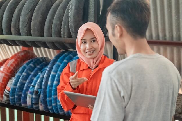 Gesluierde vrouwen in wearpack-uniformen chatten met consumenten terwijl ze in een werkplaats een digitale tablet vasthouden
