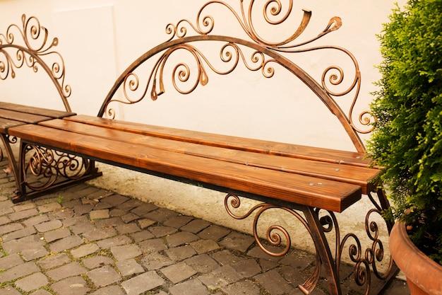 Gesmede bruine houten bank in het park met kasseien. buitenopname