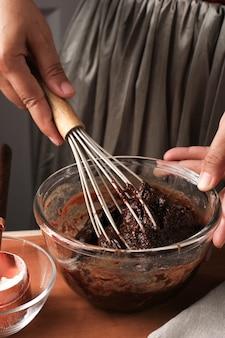 Gesmolten chocolade en cacaopoeder in een grote kom mengen om deeg/mengsel/beslag te maken voor heerlijke zelfgemaakte browniecake op houten tafel, met behulp van een ballongarde