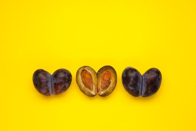 Gesmolten fruit, dubbele pruimen. lelijke vruchten in rij op gele achtergrond, plaats voor tekst. vermindering van voedselverspilling. gebruik bij het koken van onvolmaakte producten.