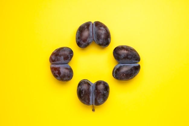 Gesmolten fruit, dubbele pruimen. lelijke vruchten op gele achtergrond met kopie ruimte. vermindering van voedselverspilling. gebruik bij het koken van onvolmaakte producten.