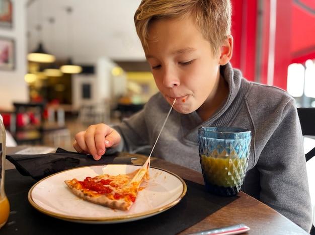 Gesmolten kaas in pizza is het lekkerst. jongen die van lunch in pizzeria geniet