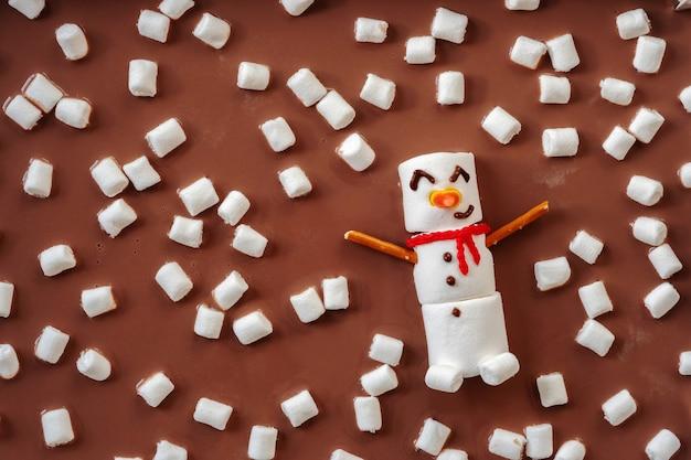 Gesmolten marshmallow-sneeuwpop die in een warme chocolademelk zwemt
