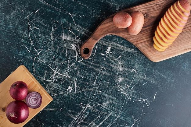 Gesneden aardappel en rode uien op een houten bord.