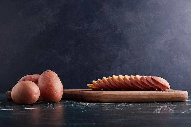 Gesneden aardappel op een houten bord.