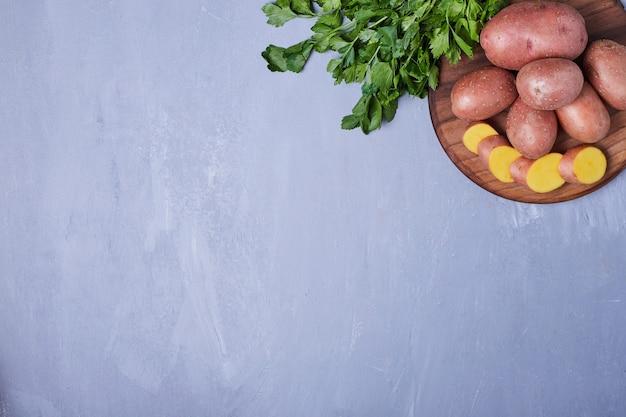 Gesneden aardappelen op blauw