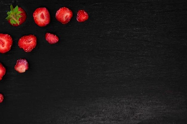 Gesneden aardbeien met bladeren op zwarte achtergrond