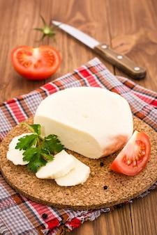 Gesneden adyghe-kaas, tomaat en peterselie op een substraat op een houten tafel
