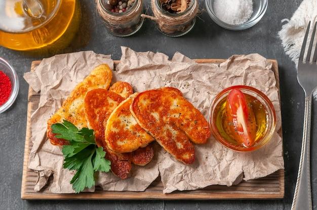 Gesneden â€â€‹halumi kaas met kruiden. op een houten plank. afgewerkt met kruiden en peterselie. naast de kaas staan kopjes met olijfolie, paprika, zout en kruiden. uitzicht van boven. grijze achtergrond
