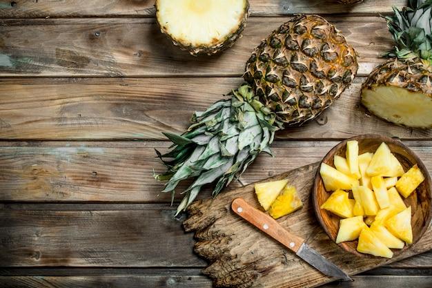 Gesneden ananas in een kom op een snijplank met een mes en een hele ananas. op houten ondergrond