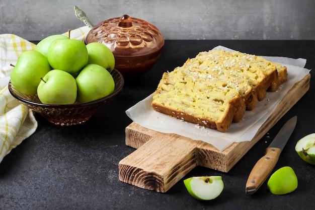 Gesneden appel en kokosnoot oaf cake op houten snijplank op donkere achtergrond