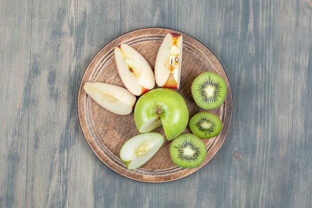 Gesneden appels met verse kiwi op een houten tafel