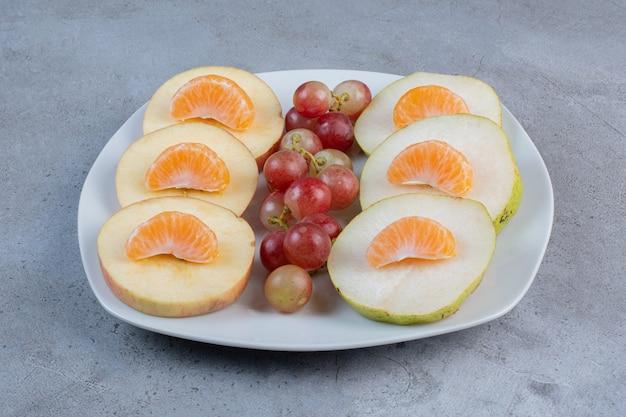 Gesneden appels, peren, mandarijnen en druiven op een schotel op marmeren achtergrond.