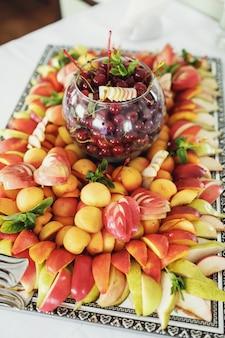 Gesneden appels, perziken, porties geserveerd op grote spiegel