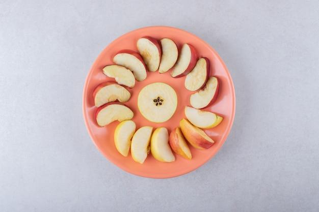 Gesneden appels rond de peer op plaat, op het marmer.