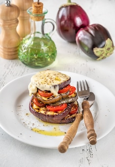 Gesneden aubergine met cherrytomaatjes en gesmolten mozzarella