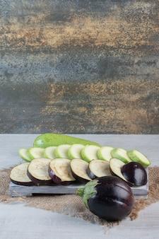 Gesneden aubergines en courgette op een houten bord. hoge kwaliteit foto