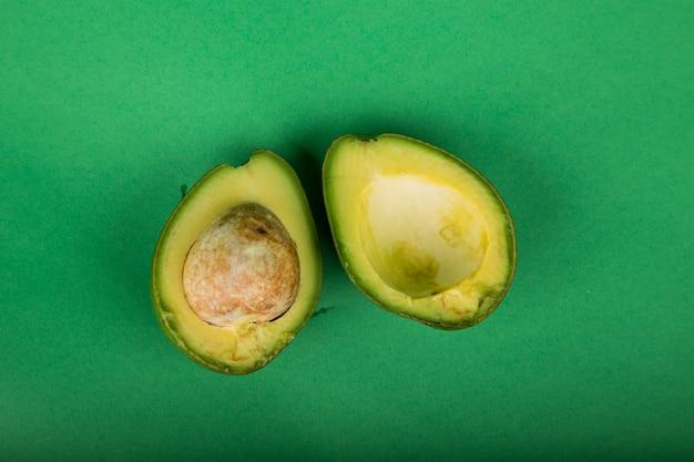 Gesneden avocado geïsoleerd op groene achtergrond