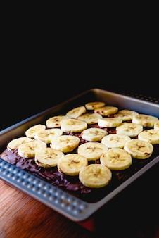 Gesneden banaan op een cake op een dienblad voor het bakken.