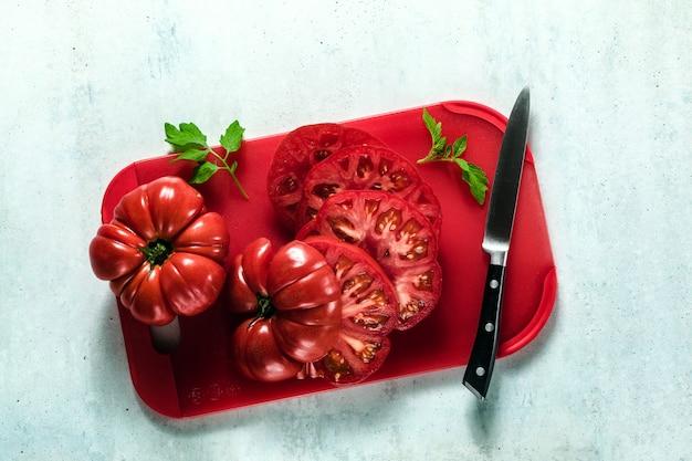 Gesneden biefstuk tomaat op een rode snijplank en een mes. gezonde zomermaaltijden koken