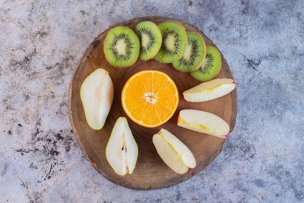 Gesneden biologisch fruit op een houten bord over rustiek.
