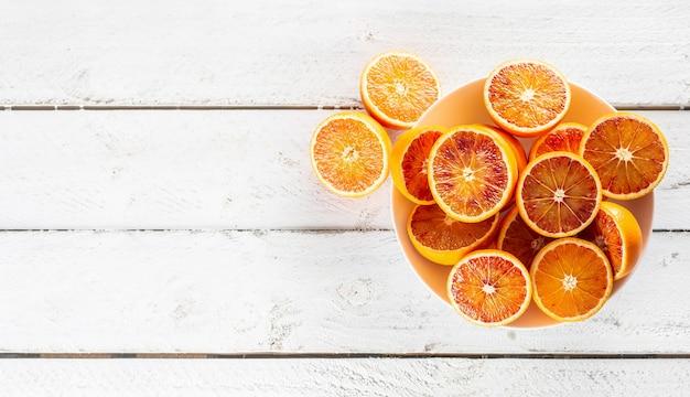 Gesneden bloedsinaasappelen in een bord op een houten witte tafel - bovenaanzicht.