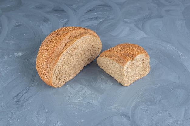 Gesneden brokken sesam bedekt brood op marmeren achtergrond.