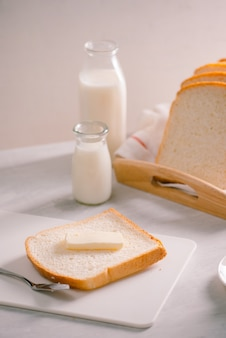 Gesneden brood bakken en boter op houten dienblad. eenvoudig ontbijt