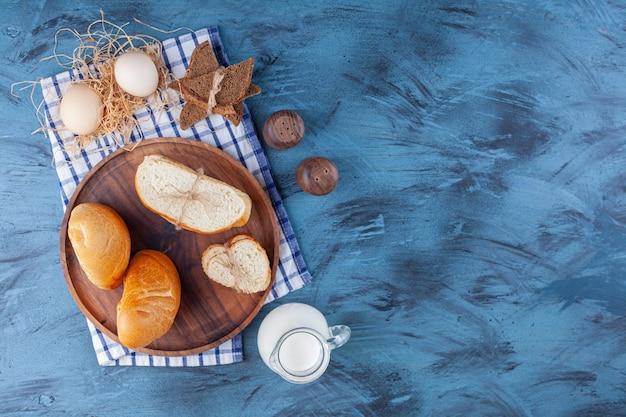 Gesneden brood, kruik melk en ei op een theedoek, op het blauw.