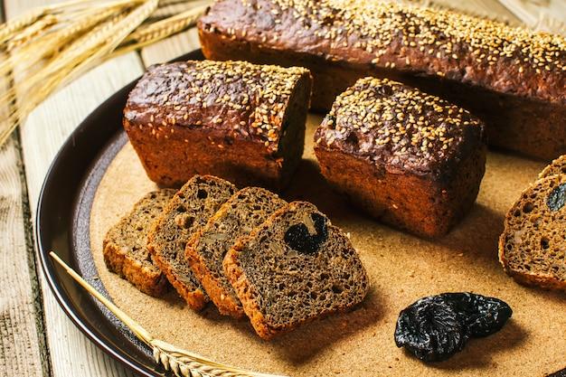 Gesneden brood met gedroogde pruimen ligt op het keukenbord. met de hand gemaakt zuurdesembrood. vers gebakken.